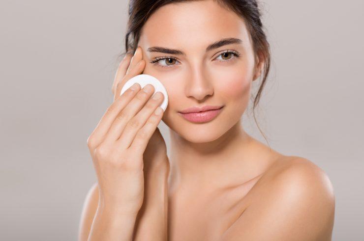 コットンで顔を拭いている女性