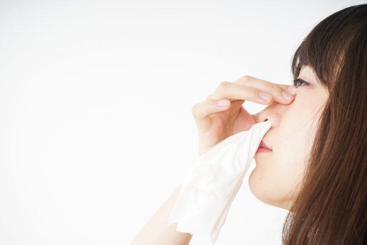 鼻をつまんでティッシュを鼻の中に入れている女性