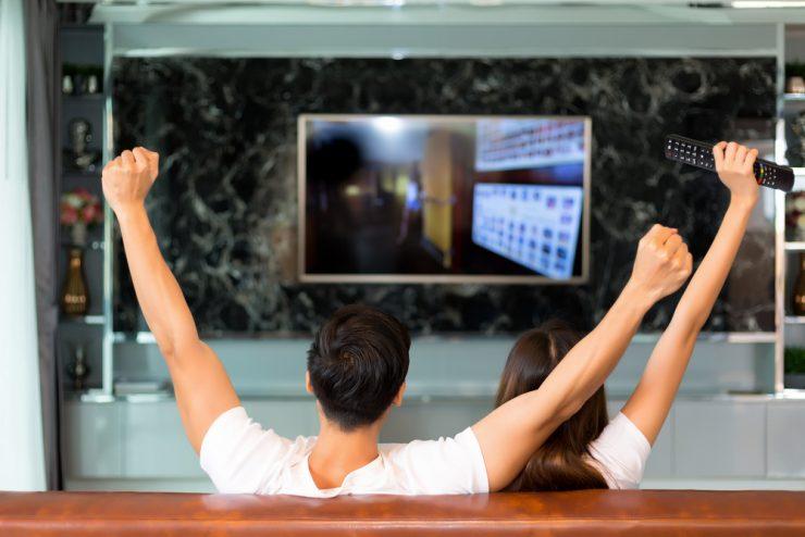 テレビを見ているカップル