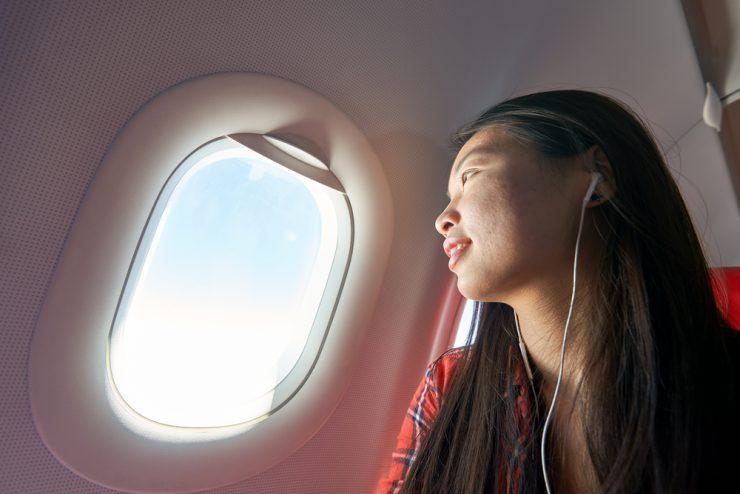 飛行機の中で外を見ている女性
