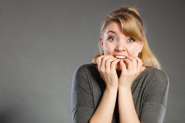 爪を噛んでいる女性