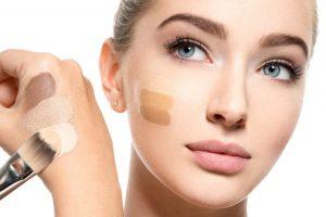 化粧下地を頬に塗ってる女性